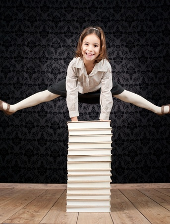 little girl jumping through a stack of books photo
