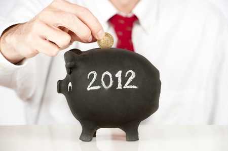 businessman putting money on a piggy bank with a year 2012 drawing photo