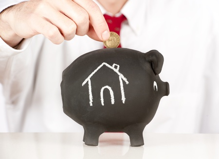 economize: businessman putting money on a piggy bank with a house sketched