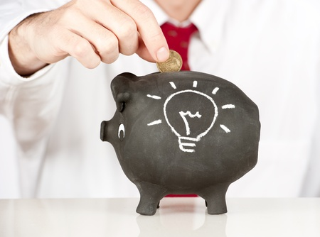 businessman putting money on a piggy bank with a lightbulb sketched photo