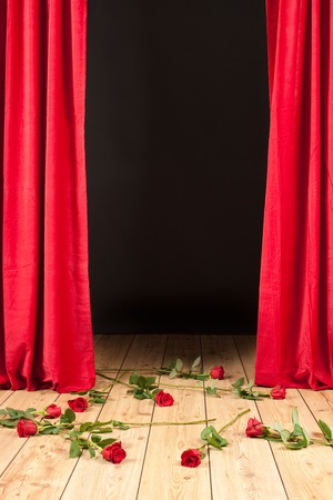 podium theater met rood gordijn, houten vloer en rozen