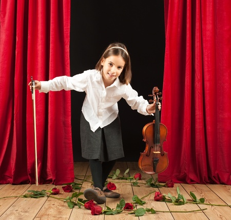 Little girl playing violin on stage theater photo