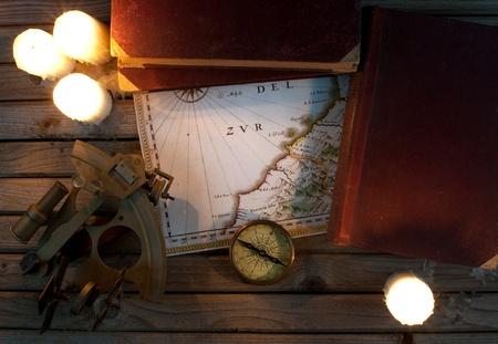 Old map, candles, sextant and books on wood background photo