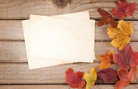 houten achtergrond met herfstbladeren en oud papier
