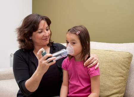 inhaling: mother using inhaler with her asthmatic daughter Stock Photo
