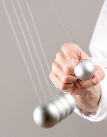 hand with newton pendulum photo