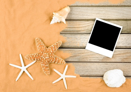 sand and wood background with instant photo frame photo