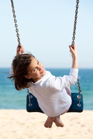 Bambina oscillazione con il mare sullo sfondo