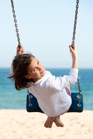 playground ride: Little girl swinging with the sea in the background