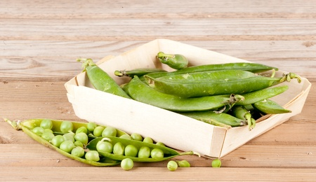 viands: pods of green peas on wood background Stock Photo