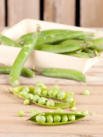 pods of green peas on wood background Stock Photo - 12173854