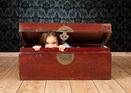 'young things': little girl inside an ancient trunk with a vintage background