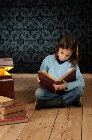 history books: little girl reading a book with a retro background