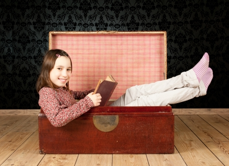 'young things': young girl inside an ancient trunk reading a book with a vintage background Stock Photo