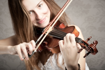 young woman playing violin on gray background Stock Photo