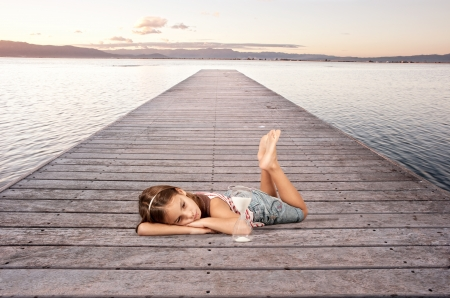 little girl looking an hourglass on a wharf photo