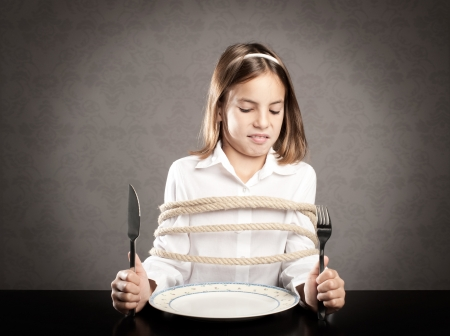 little girl roped sitting at table holding forks in front of a dish Stock Photo - 17565434