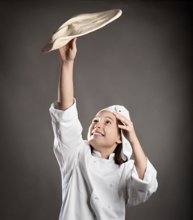 young chef working the dough for pizza photo