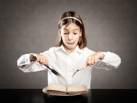 little hungry girl sitting at table holding forks in front of a book