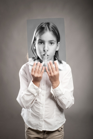 portrait of girl holding a photography of her with silence gesture Stock Photo - 17565370