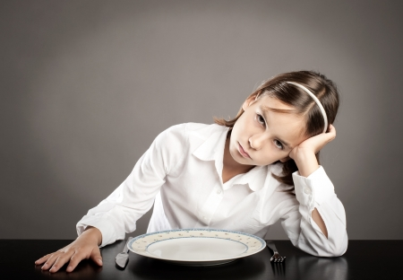 little girl sitting at table in front of an empty dish Stockfoto