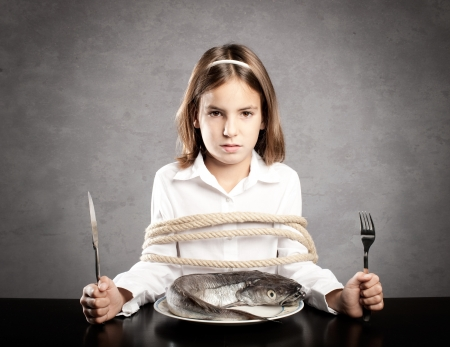 little girl roped sitting at table holding forks in front of a whole raw fish photo