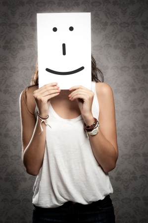 young woman holding smile symbol in front of her face Stock Photo - 17601322