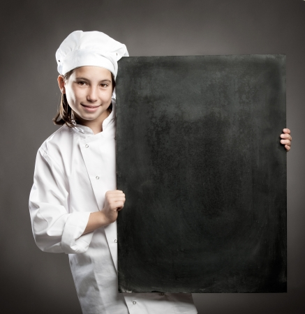 young chef holding menu chalkboard photo