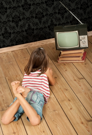 little girl watching old retro tv photo