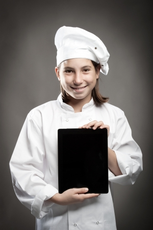 beautiful young chef holding a tablet on gray background photo