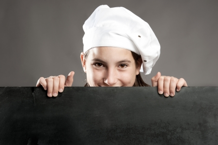 young chef holding menu chalkboard photo