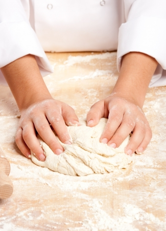 young chef working the dough with hands