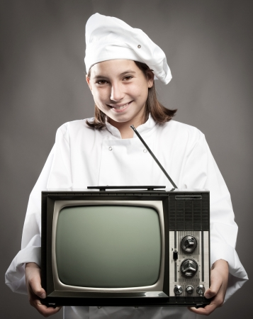 beautiful young chef  holding television on gray background photo