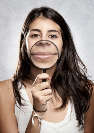 young woman showing mouth through magnifying glass Stock Photo - 17601302