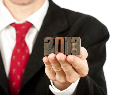 businessman holding year 2013 letterpress on white background photo
