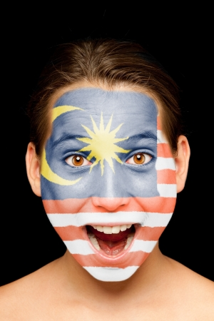 portrait of girl with malaysian flag painted on her face