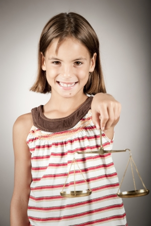 justice scales: little girl holding justice scale Stock Photo