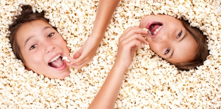 two girls buried in popcorn photo