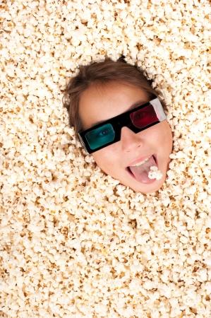 persona feliz: chica joven enterrado en las palomitas de maíz con gafas 3D