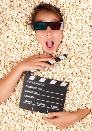 giovane ragazza sepolta nel popcorn con ciak film