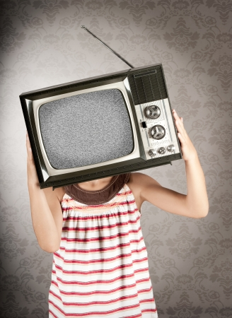 little girl with old retro television on her head photo