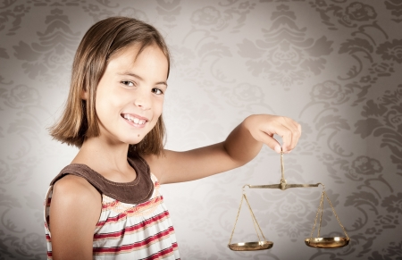 innocence: little girl holding justice scale Stock Photo