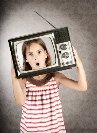 little girl with old retro television on her head
