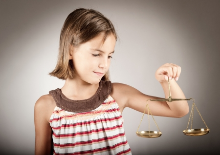 little girl holding justice scale Stockfoto