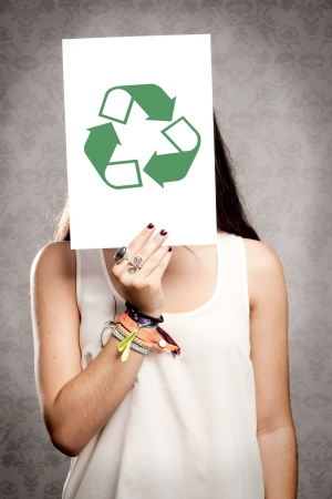 portrait of girl holding a recycling symbol in front of her face photo