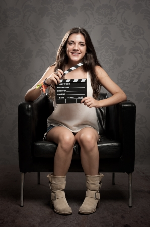 young woman holding a movie clapper board photo