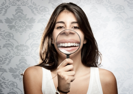 young woman showing teeth through magnifying glass Stock Photo - 17601291