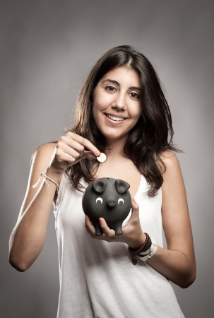 young woman saving money on a piggy bank Stock Photo - 17601293