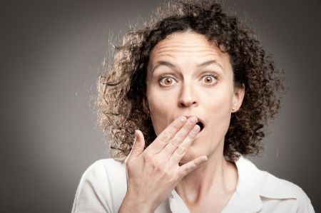 hand on mouth: woman with hand over open mouth Stock Photo