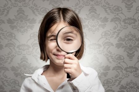 bambina guardando fotocamera attraverso la lente di ingrandimento